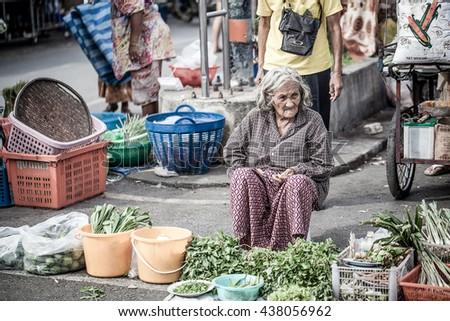 Ratchaburi , Thailand - JUNE 11, 2016 : Old women seller wating for customer on street market.  - stock photo