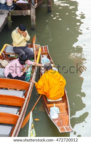 Ratchaburi ,Thailand - March 20 2016 : Buddhist monk on boat in morning at Damnoen Saduak Floating Market, tourists visiting by boat, located in Ratchaburi, Thailand.