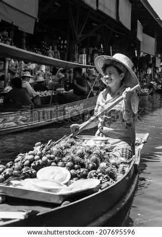 Ratchaburi, Thailand - May 24, 2014: Thai locals sell food and souvenirs at famous Damnoen Saduak floating market on  May 24, 2014 in Thailand, in the old traditional way of selling from small boats.