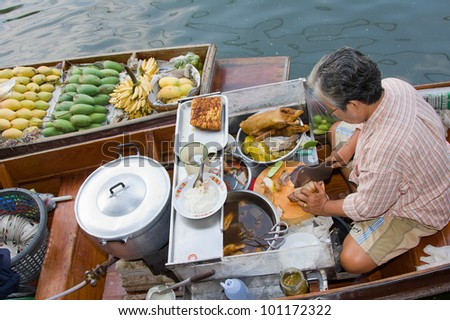 RATCHABURI, THAILAND - NOV 30: A woman makes Thai food at Damnoen Saduak floating market on November 30, 2011 in Ratchaburi, Thailand. Its popular for traditional style Thai food and old Thai culture.