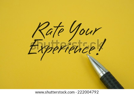 Rate Your Experience! note with pen on yellow background - stock photo
