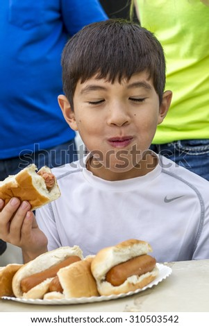 Rathdrum, Idaho USA - August 15, 2015. A young boy participates in a hot dog eating contest during taste of Rathdrum in Idaho USA August 15, 2015. - stock photo