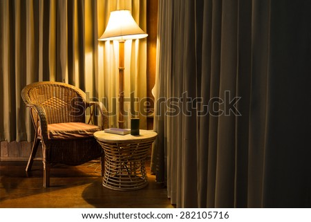 Rattan chair and stool under the light from the lamp with bamboo cup and the book surround by beautiful curtain. - stock photo