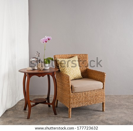 Rattan chair in a patio garden lounge setting - stock photo