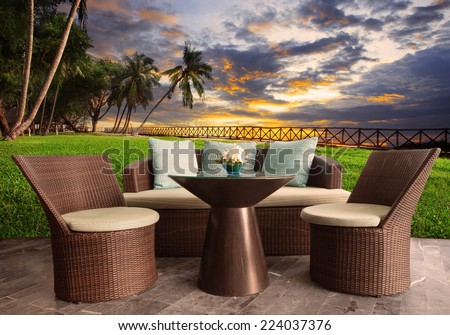 rattan chairs in outdoor terrace living room against beautiful sunset sky - stock photo