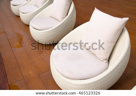 rattan chairs with pillows  beside pool , relaxing