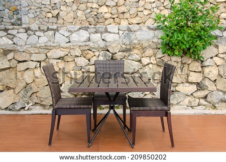 Rattan table and chairs in cafe against stone wall. - stock photo