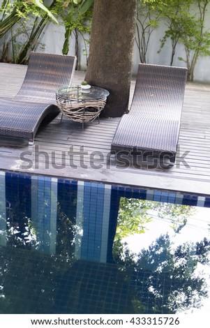 rattan wicker sunbed beside swimming pool - stock photo