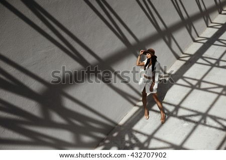 raven haired indian lady posing in geometrical shadows of metal stractures