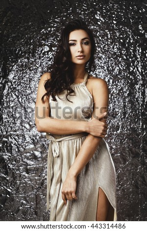 raven haired indian lady posing in studio against glossy foil background