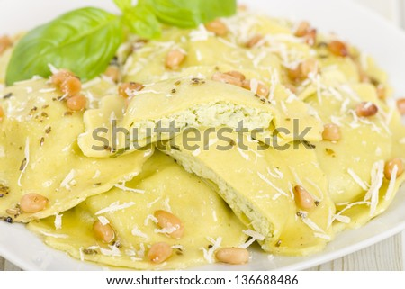 Ravioli - Italian egg and spinach pasta with basil, ricotta and pine nuts filling with brown butter, pine nuts and sage sauce. Garnished with parmigiano-reggiano. - stock photo
