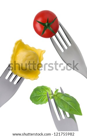ravioli pasta basil and cherry tomato on forks against white background - stock photo