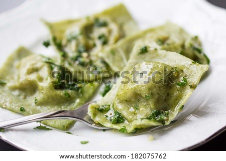 Ravioli pasta from green dough with mushroom stuffing, oil, parsley, vegetarian dish - stock photo