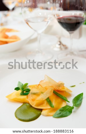 Ravioli with pesto sauce and potato chips on restaurant table - stock photo