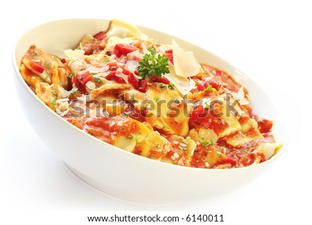 Ravioli with roasted vegetable sauce, garnished with shaved parmesan and parsley. - stock photo