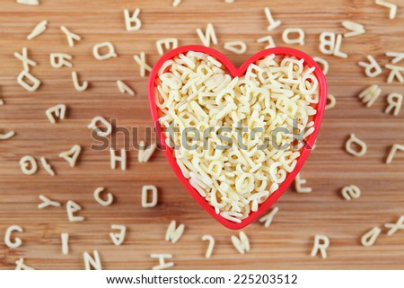 Raw alphabet soup pasta in a heart bowl. Close-up. - stock photo