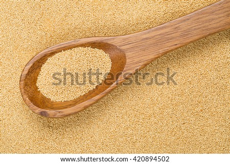 Raw amaranth seeds on wooden spoon on amaranth seeds background
