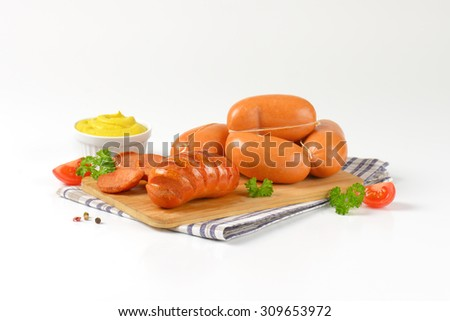 raw and roasted sausages on wooden cutting board - stock photo