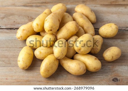 raw baby potatoes on rustic wooden background - stock photo