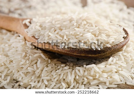 Raw basmati rice in  a wooden  spoon . Selective focus - stock photo
