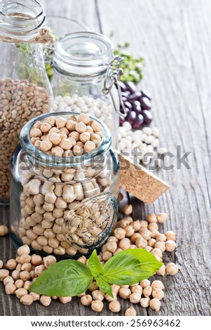 Raw beans and lentils in glass jars and bottles - stock photo