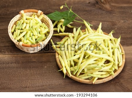 Raw beans, fresh legumes and its stem in the basket - stock photo
