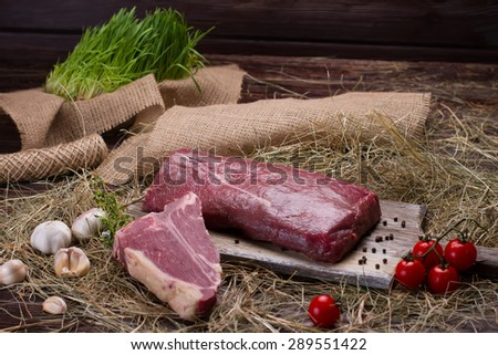 Raw beef and T-bone with tomatoes on a wooden board. Beautiful interior. - stock photo