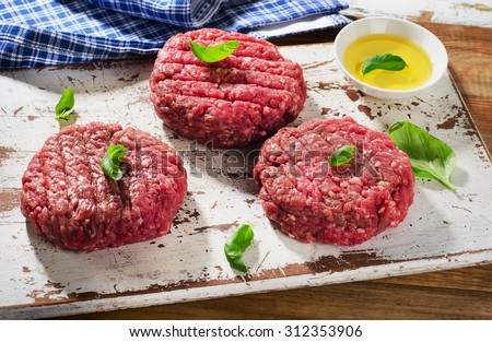 Raw beef burger patties on  cutting board. Selective focus - stock photo