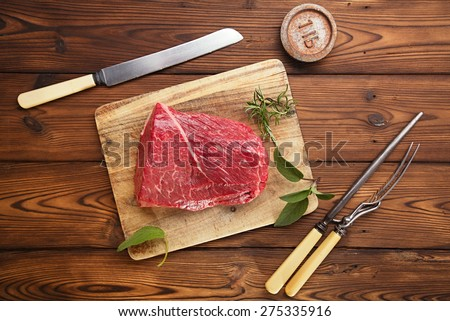 raw beef meat fillet  on wooden  table with meat fork and 1lb iron weight - stock photo