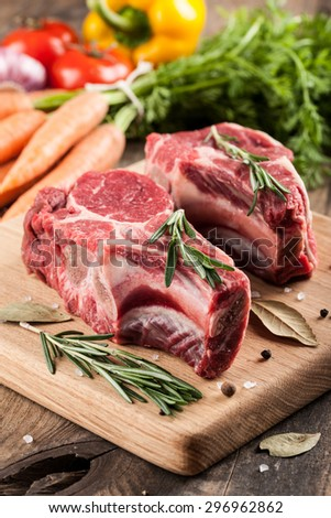 Raw beef meat on cutting board and fresh vegetables on wooden table