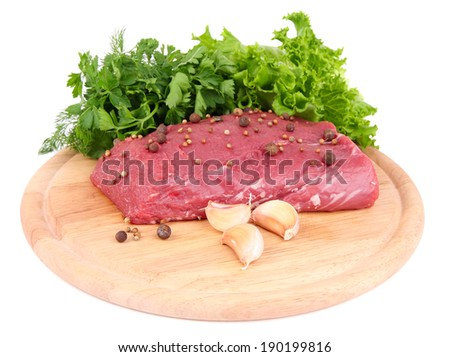 Raw beef meat with spices and greens on wooden cutting board isolated on white