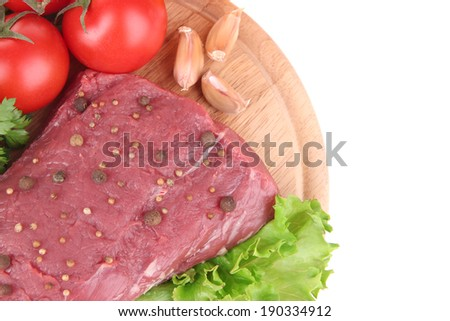 Raw beef meat with vegetables on wooden cutting board isolated on white - stock photo