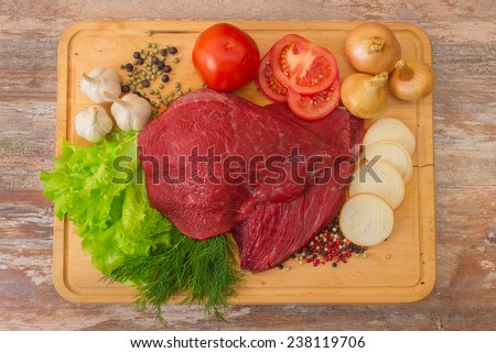 raw beef meat with vegetables on wooden plate - stock photo