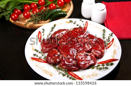 Raw beef medallions served on plate with rosemary, pepper and spices - stock photo