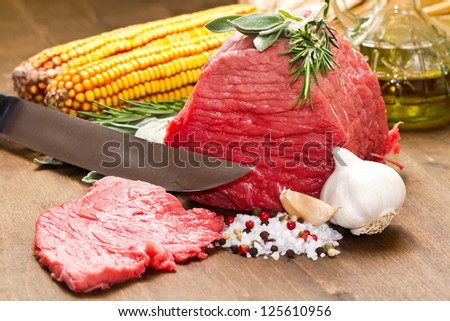 Raw beef on wooden table with rosemary ,sage , salt, cob and garlic - stock photo