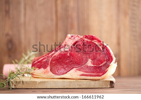raw beef rib steak with bone on wooden board and table - stock photo