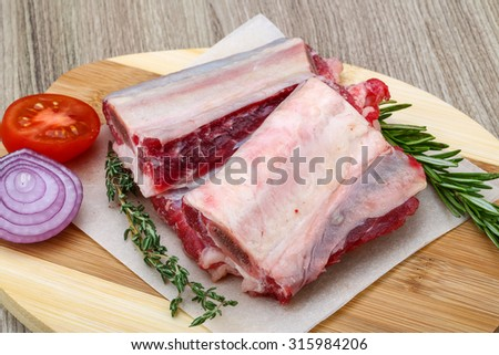 Raw Beef ribs with rosemary and thyme on wood background - stock photo