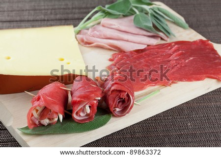 raw beef rolls with ham and cheese with raw ingredients over a wood board - stock photo