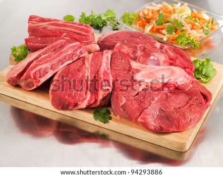 Raw beef shank steak on a cutting board and steel table. - stock photo