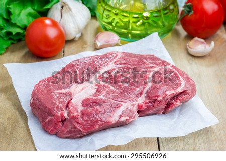 Raw beef steak on a parchment paper - stock photo