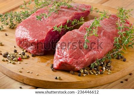 Raw beef steak on   board. Selective focus - stock photo
