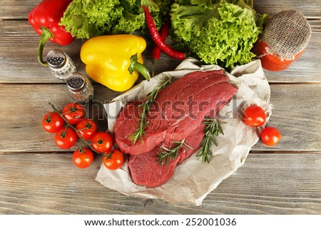 Raw beef steak on paper with vegetables and greens on wooden background - stock photo