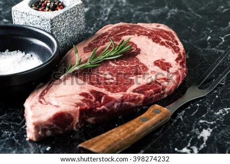 Raw beef steak ribeye loin marble on a dark marble background - stock photo