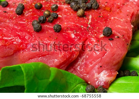 Raw beef steak with black pepper on the lettuce leaf - stock photo