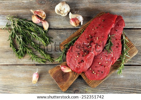 Raw beef steak with rosemary and garlic on cutting board on wooden background - stock photo