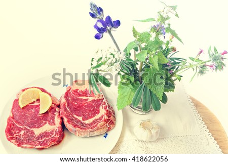 Raw beef steak with spices (sliced lemon and garlic) ready for cooking. Wild herbs and flowers on the wood board. Food ingredients and herbs still life.  Toned colors vintage image - stock photo