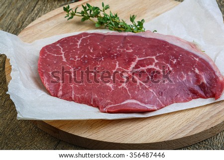 Raw beef steak with thyme - ready for cooking - stock photo