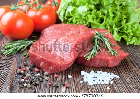 Raw beef steak  with vegetables and spices on brown wooden background - stock photo