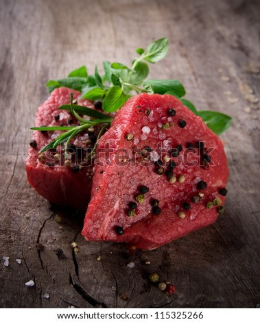 Raw beef steaks on wooden table - stock photo