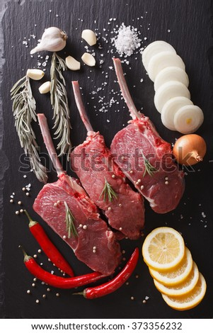Raw beef steaks with ingredients on a black stone table closeup. vertical top view - stock photo